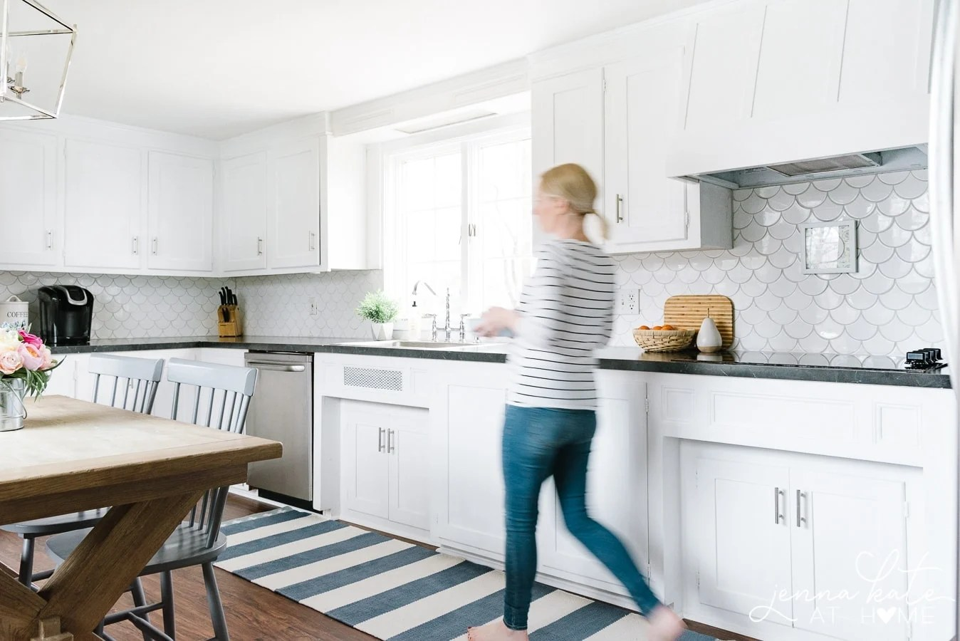woman walking across striped kitchen runner