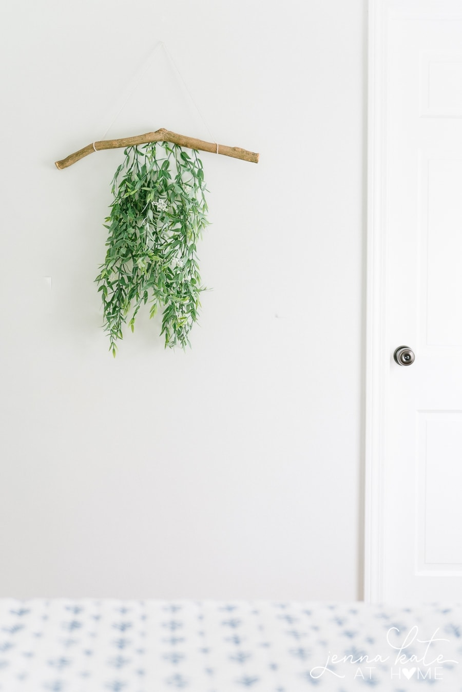 Branch wall hanging with attached green foliage on wall, next to bedroom door