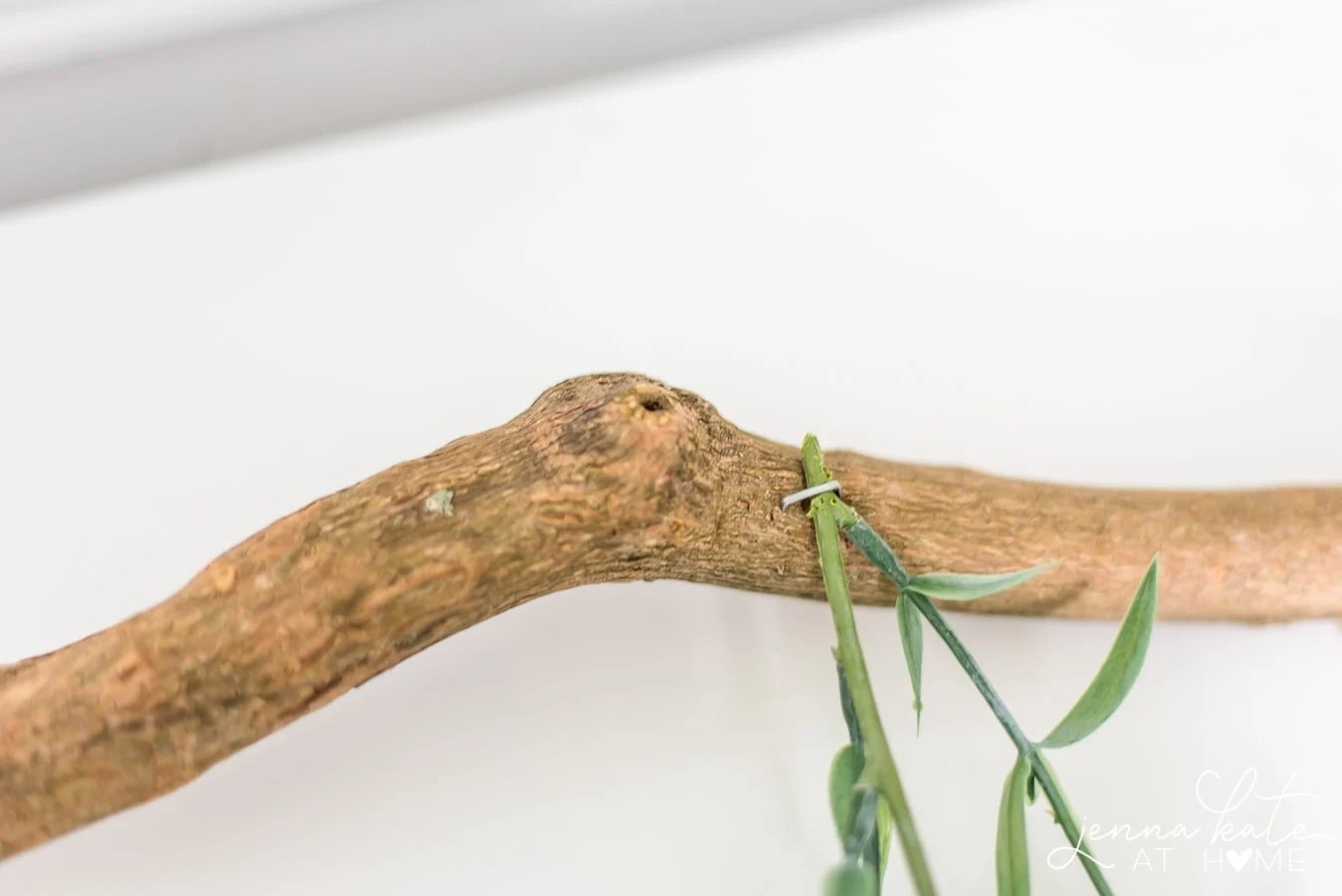A close-up of the end of the clipped green garland seured to the branch with a heavy-duty staple