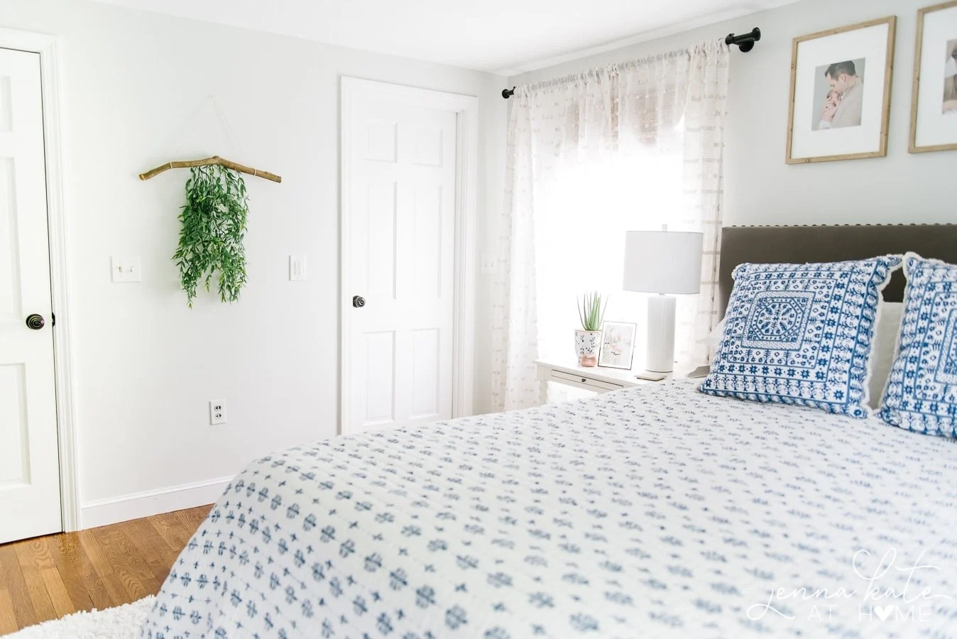 Photo of bedroom, with branch wall hanging near door, near bed with blue and white coverlet & pillows