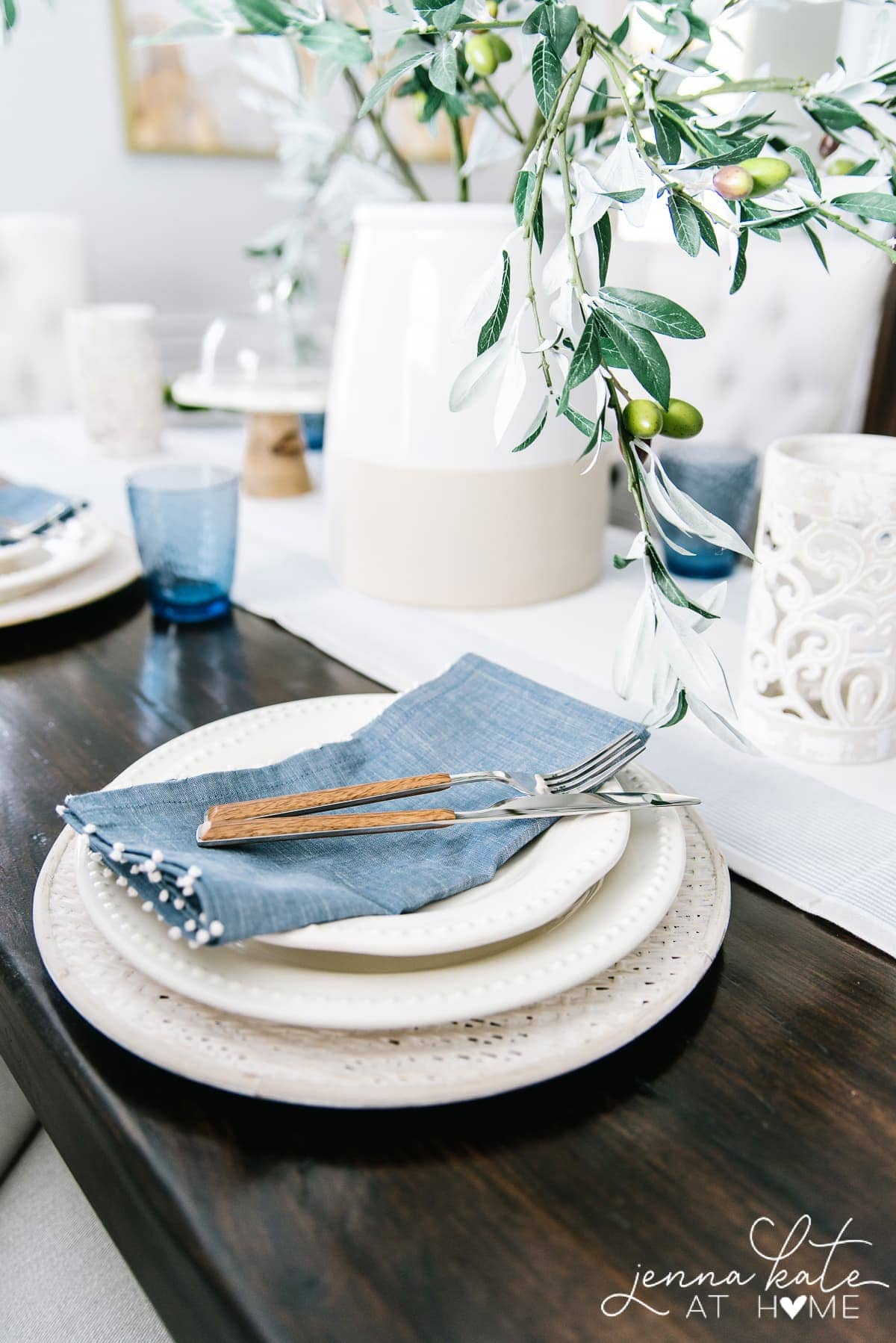 The blue linen napkins and coastal blue glassware give this coastal inspired tablescape pops of color