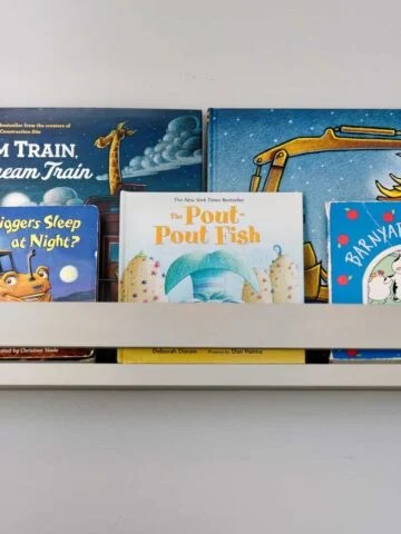 Various children's books placed neatly in a light grey wooden ledge shelf on wall