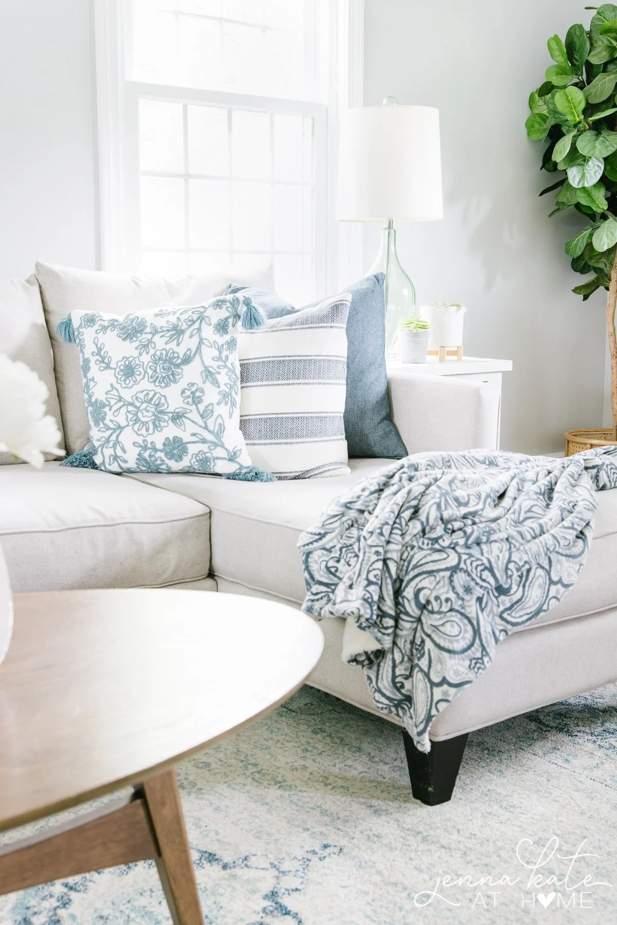 Decorating the living room couch with blue throw pillows and a matching blanket