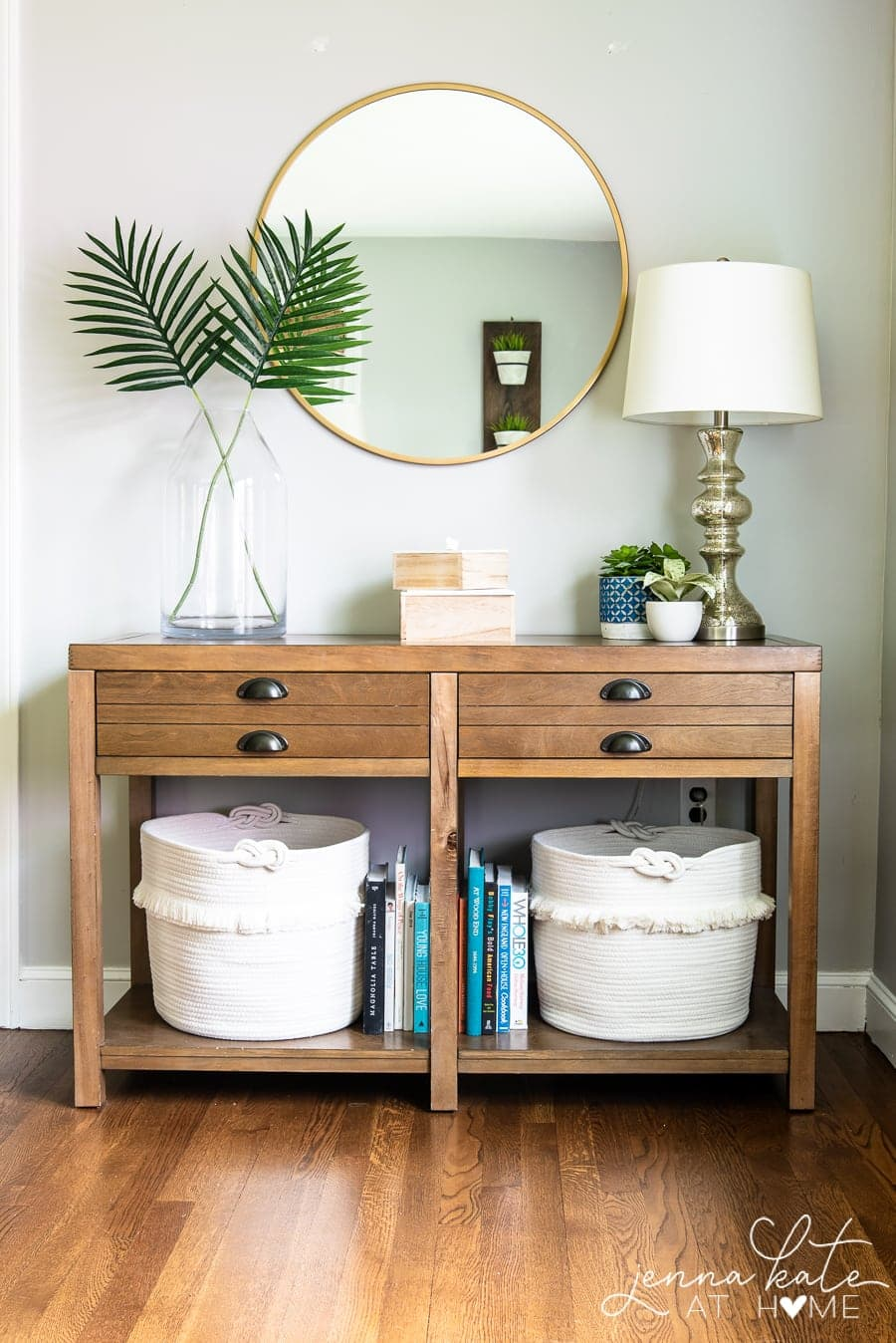 console table decorated for summer with palm fronds and white baskets underneath
