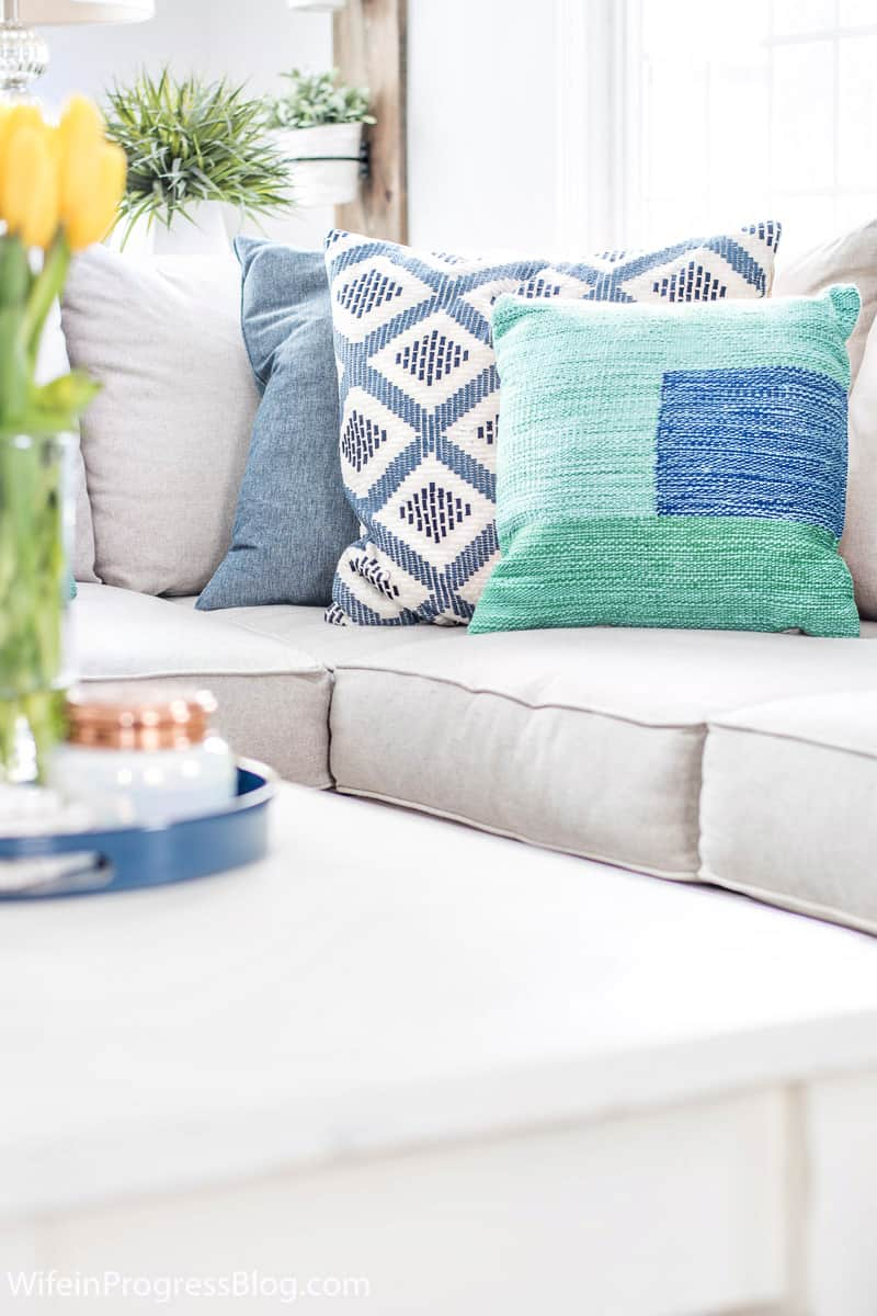 sofa with colorful blue and green throw pillow