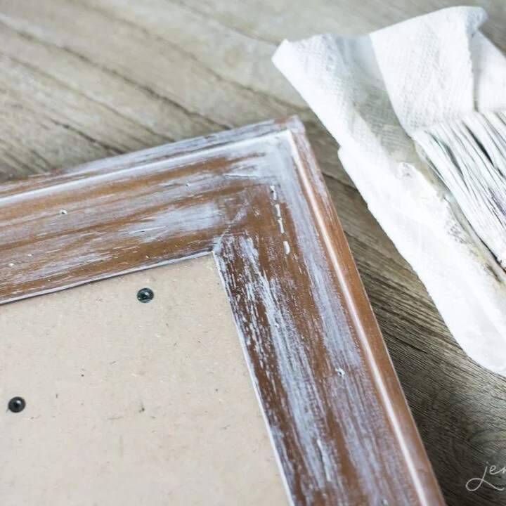 A wooden frame showing the beginning stages of whitewash treatment