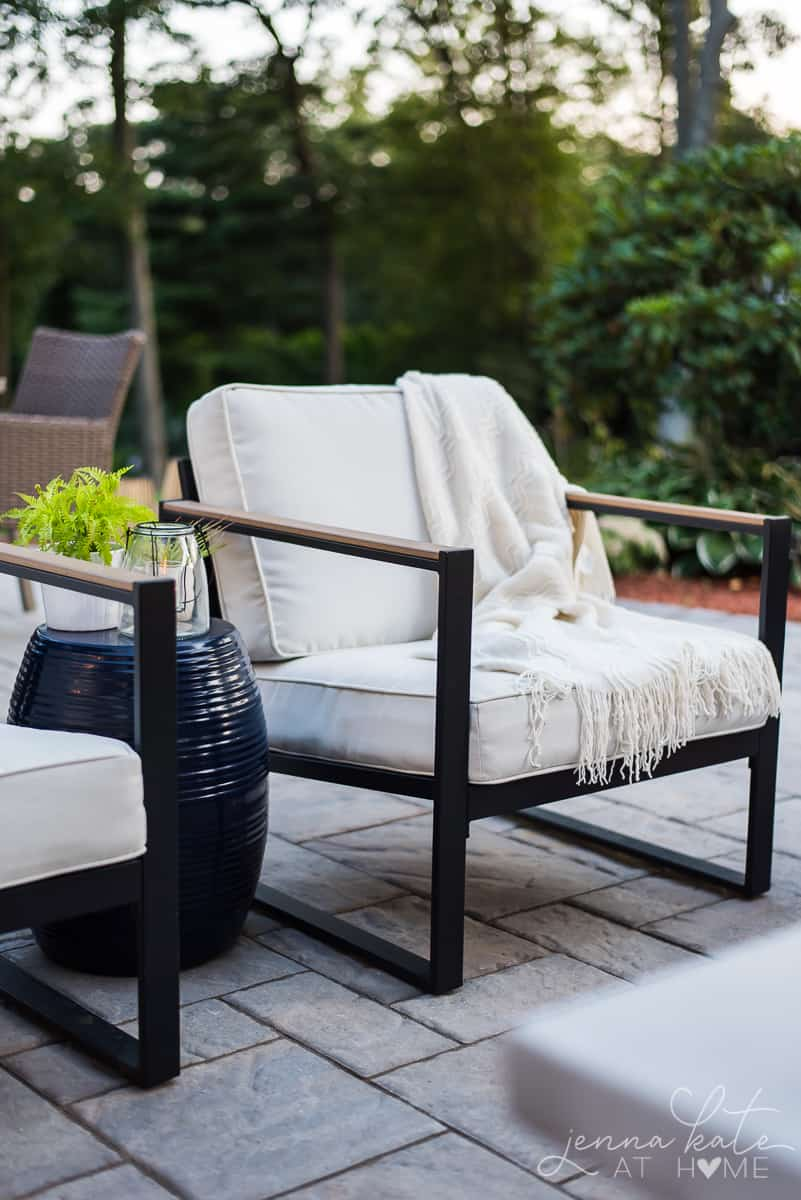 Stylish patio chairs with white curtains and a warm throw blanket