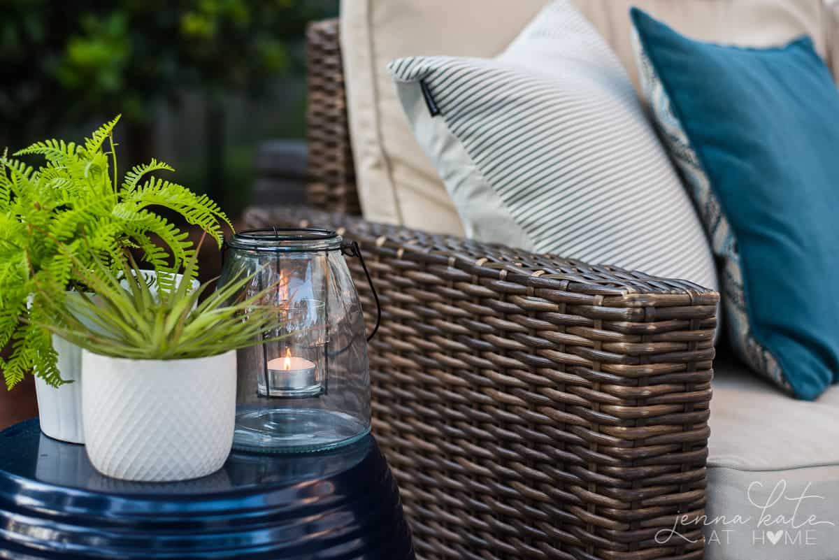 Our backyard patio has coastal decor like plants and blue and white throw pillows