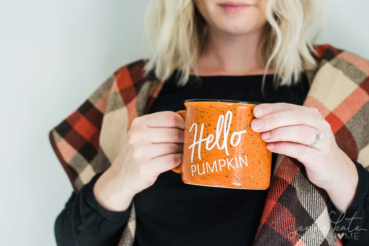 Author, wearing seasonal fall wrap, holding finished DIY mug with vinyl lettering