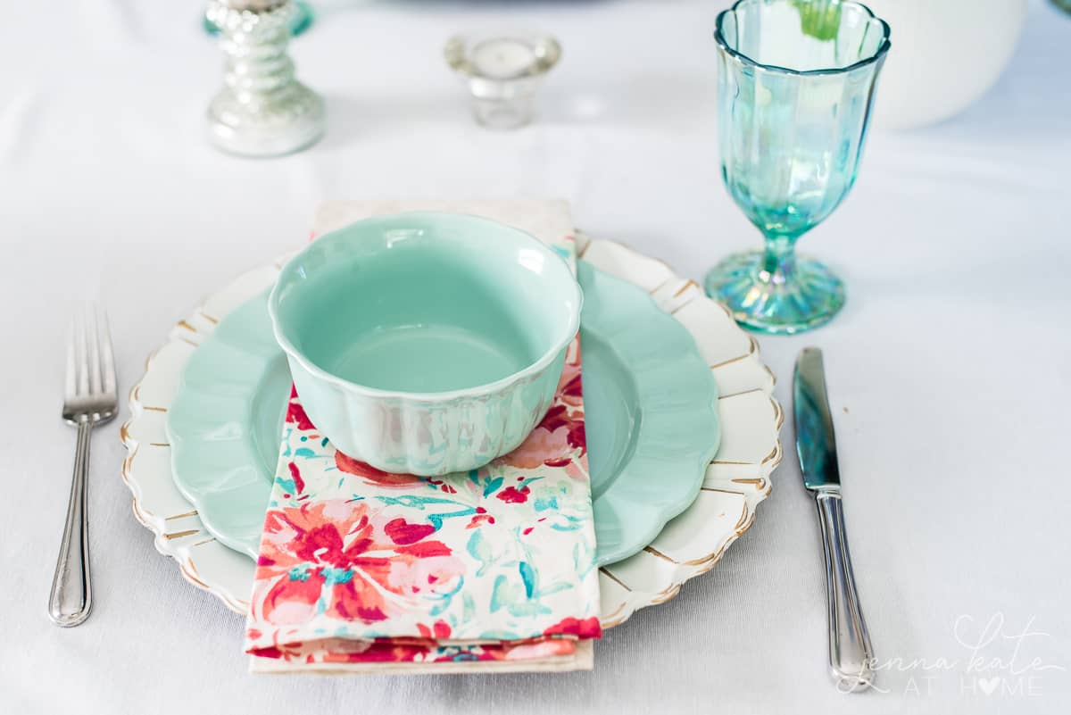 Seafoam green dishware paired with matching glasses and bright floral napkins