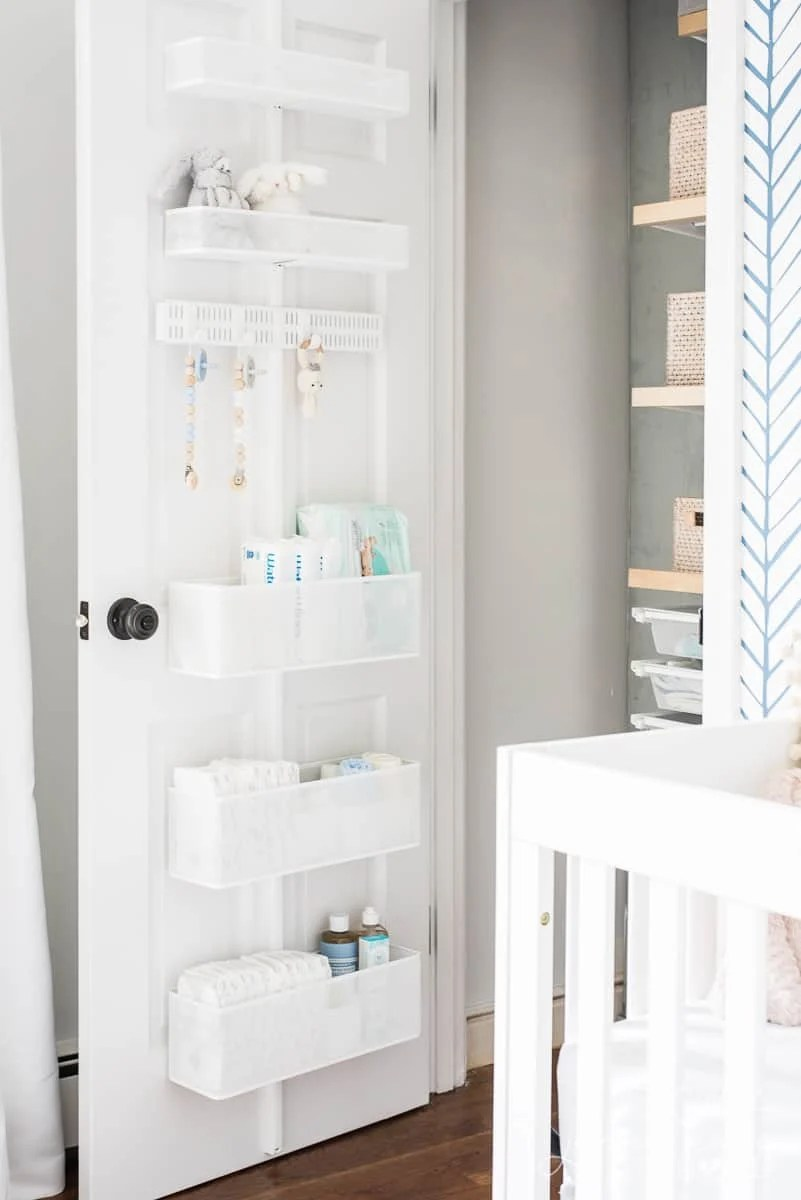 Shelves on back of a nursery closet door that store diapers and baby wipes
