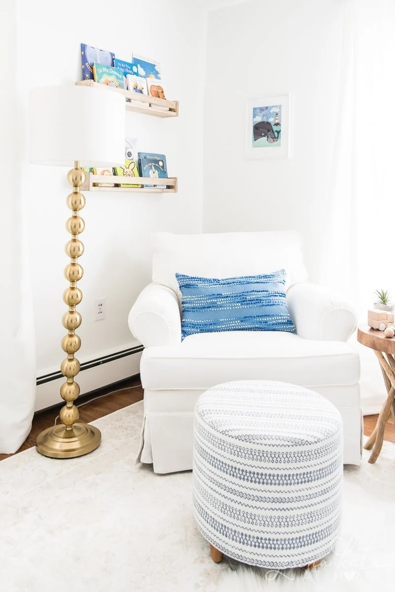 White nursery rocking chair with gold lamp and blue pillow and foot stool
