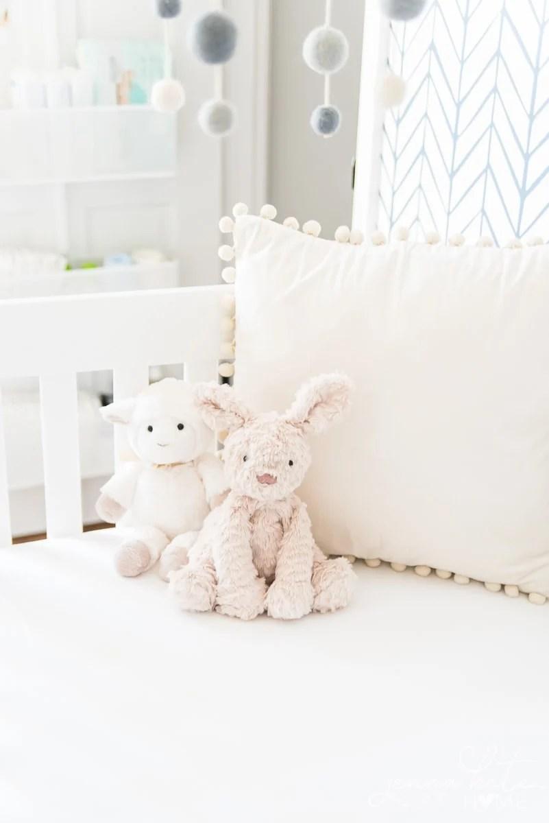 A teddy bear sitting on top of a crib