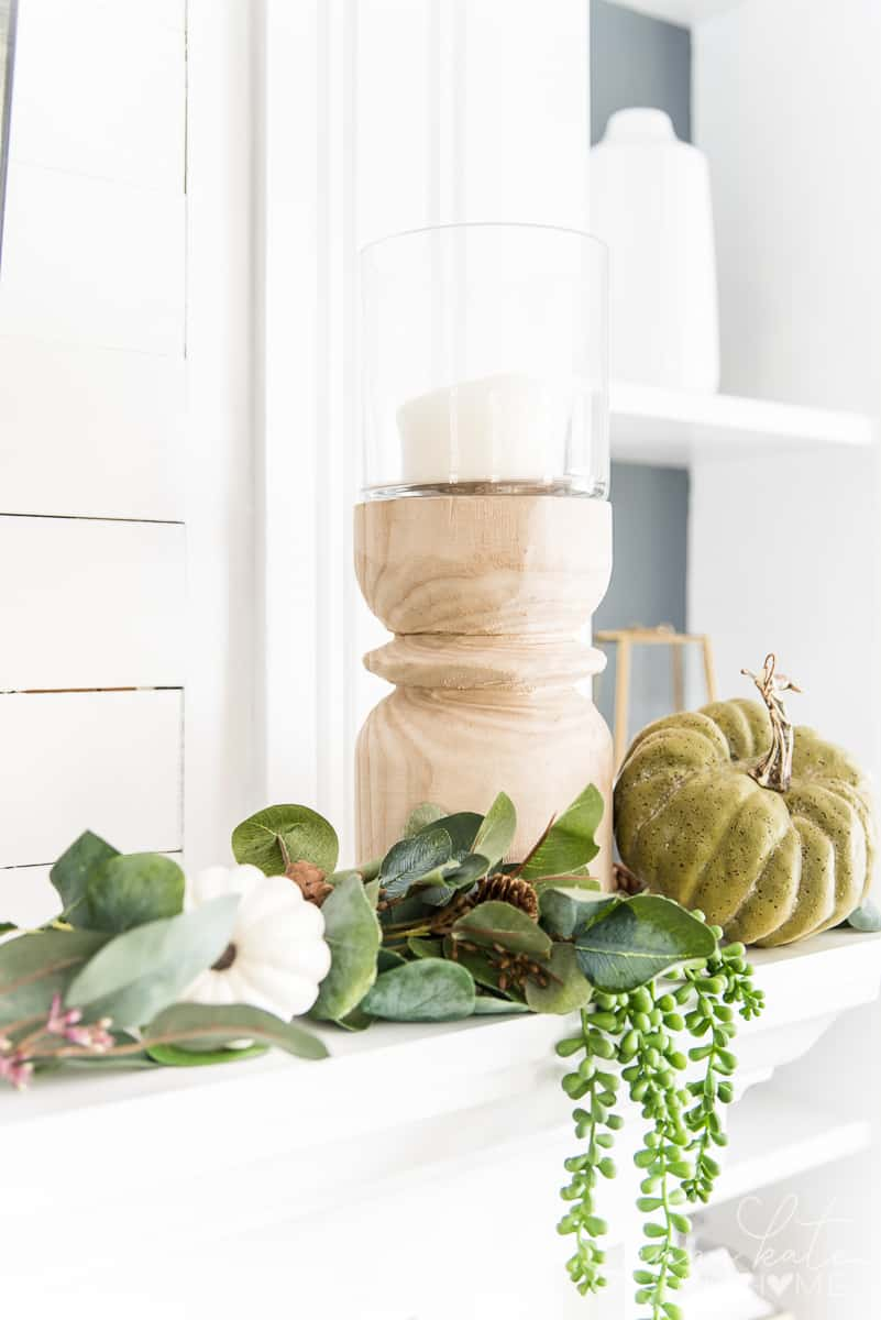Wooden hurricane candle holder with faux greenery and pumpkins on a mantel