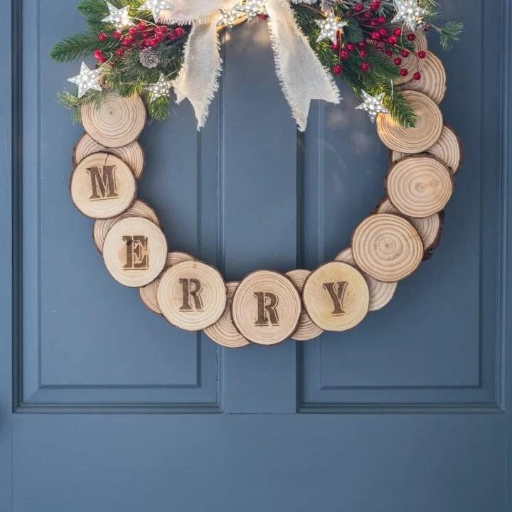 Wood slice holiday wreath hung on a blue door