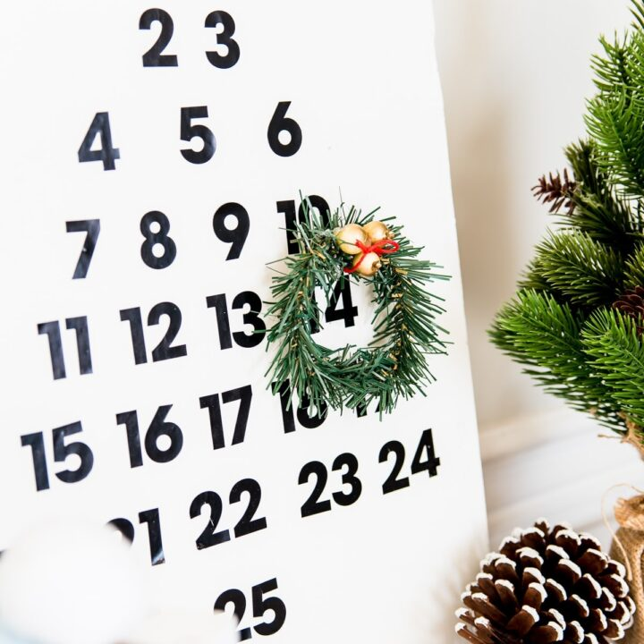 Wooden calendar painted white, with black number stickers for days 1 - 25, and a tiny wreath on day 14