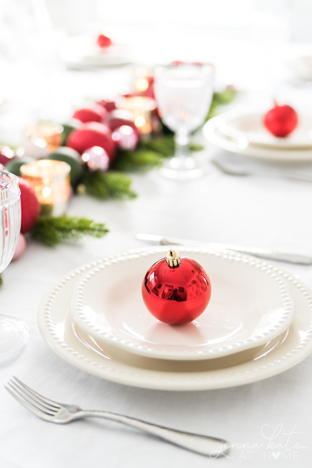 Festive Christmas table centerpiece using tree ornaments, votives and greenery