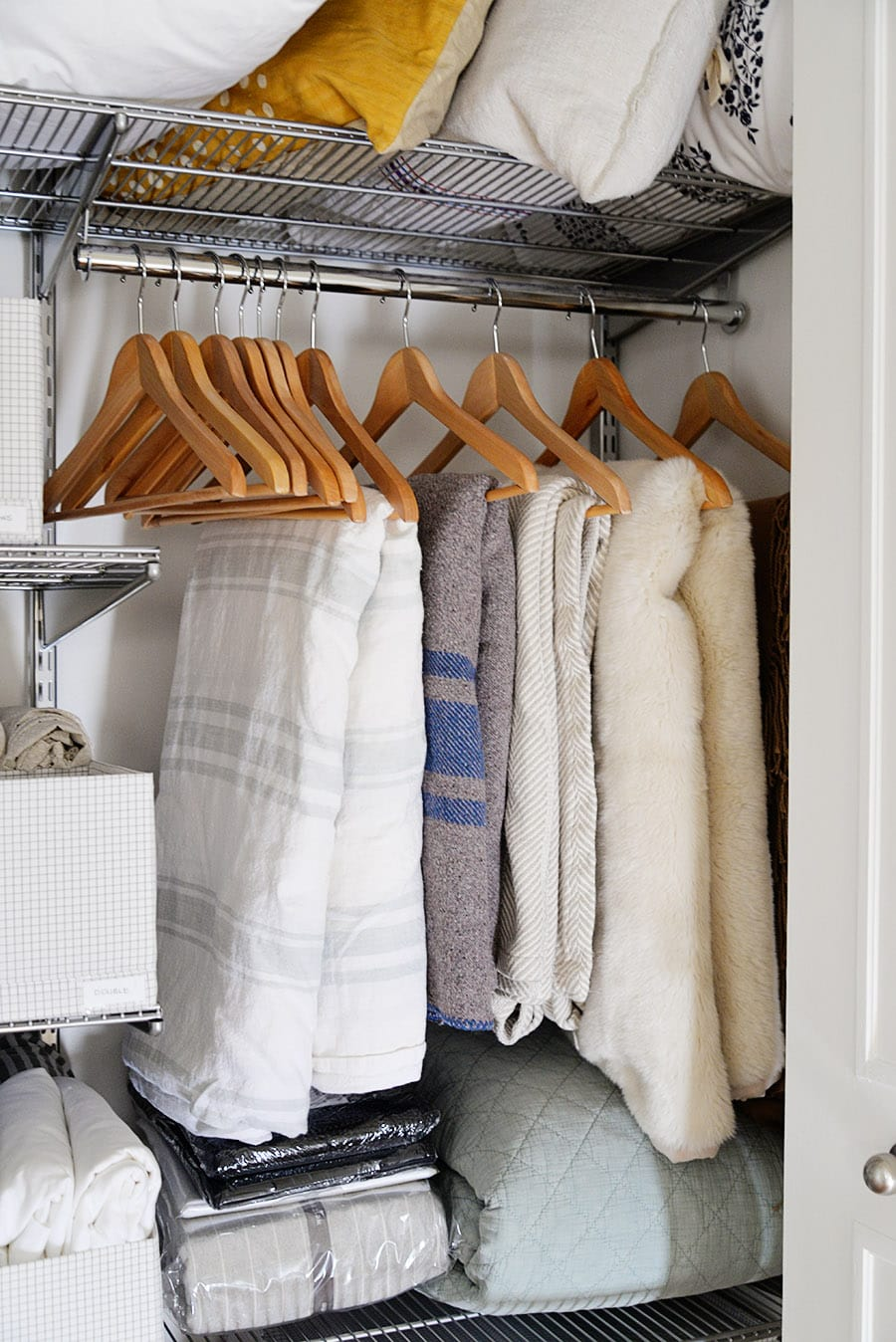 comforters and duvets hung on hangers inside a closet