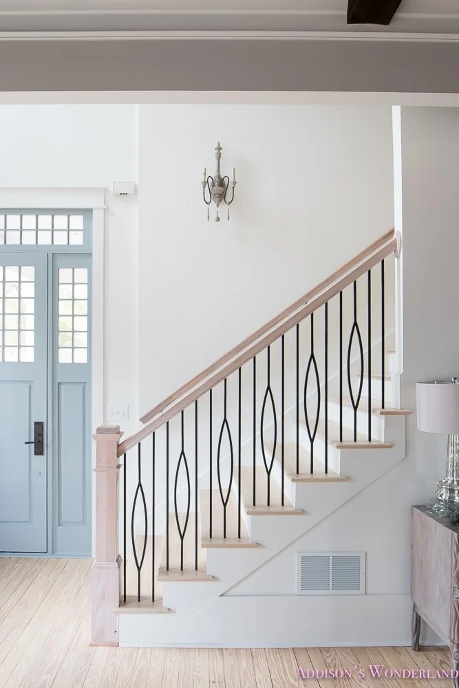 light and bright foyer painted white with bleached wood handrails and floors