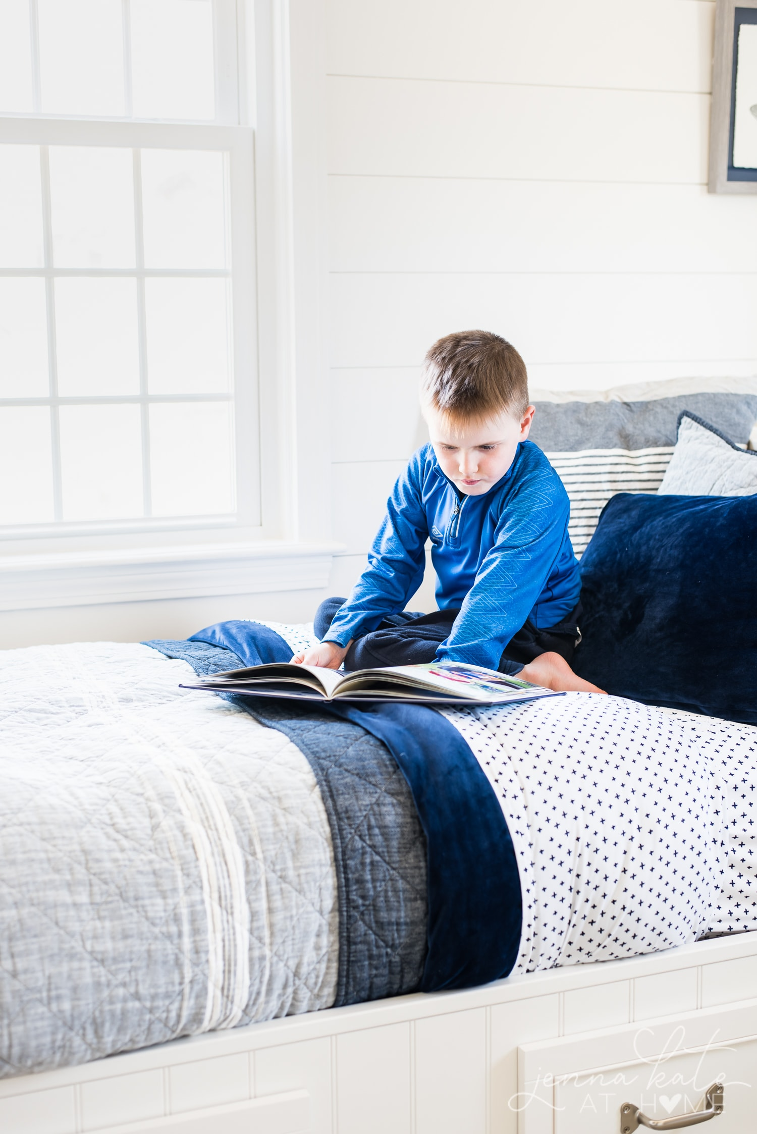 Young boy reading on the bed with layered bedding - small print bedsheets, solid navy duvet cover and gray quilt.