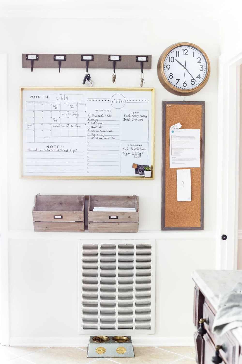 Large whiteboard calender, key hooks, clock, bulletin board and wooden crates for filing papers