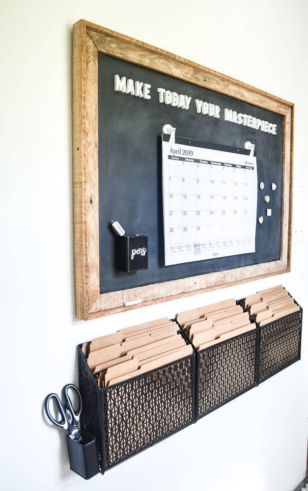 Framed blackboard command center with black filing bins underneath
