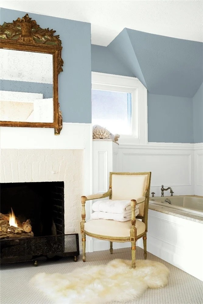 Santorini Blue bedroom paired with white wainscoting brings out the blue in this blue-gray paint color