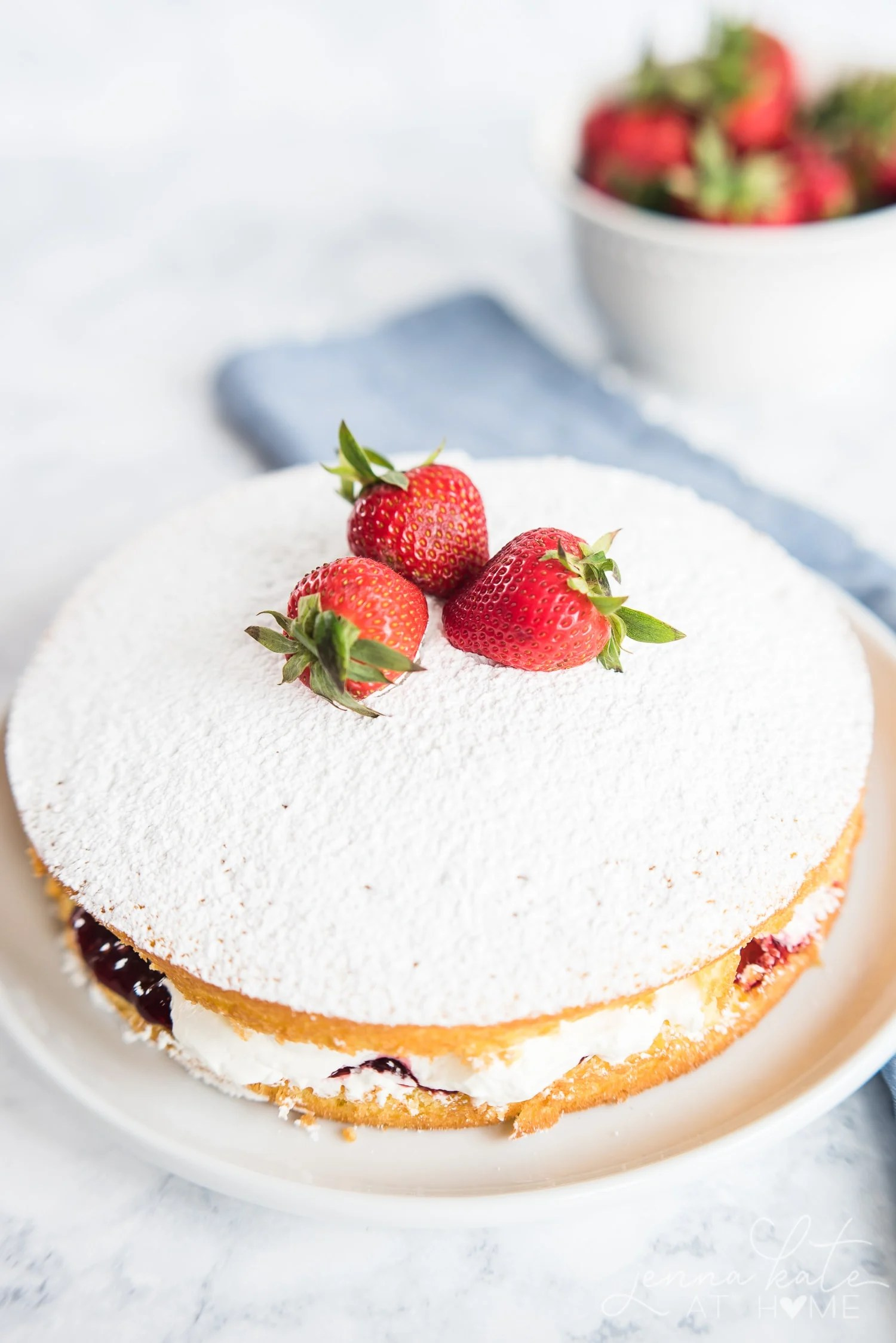 Top of victoria sponge cake, dusted with powdered sugar and topped with fresh whole strawberries
