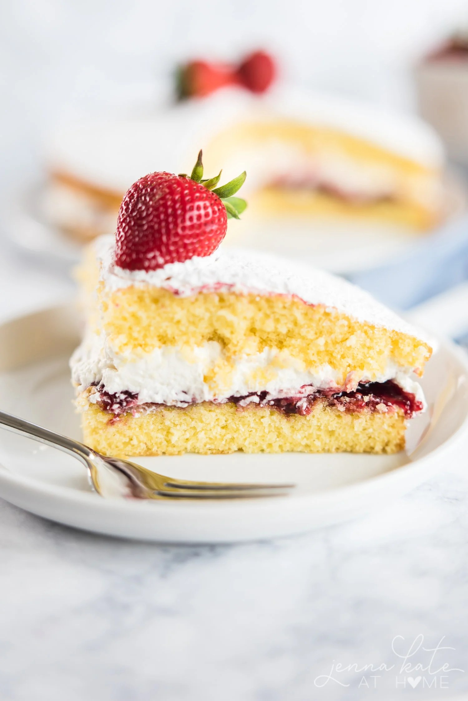 A slice of Victoria Sponge Cake is filled with a layer of raspberry filling and fresh whipped cream