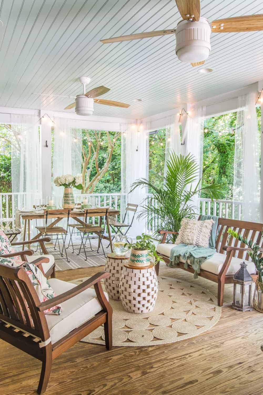 Boho style back porch with curtains and ceiling fans
