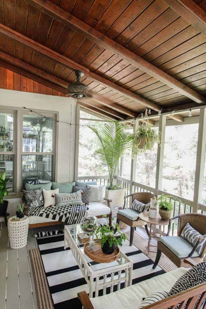 Screened in porch with dark wood ceilings and boho style decor
