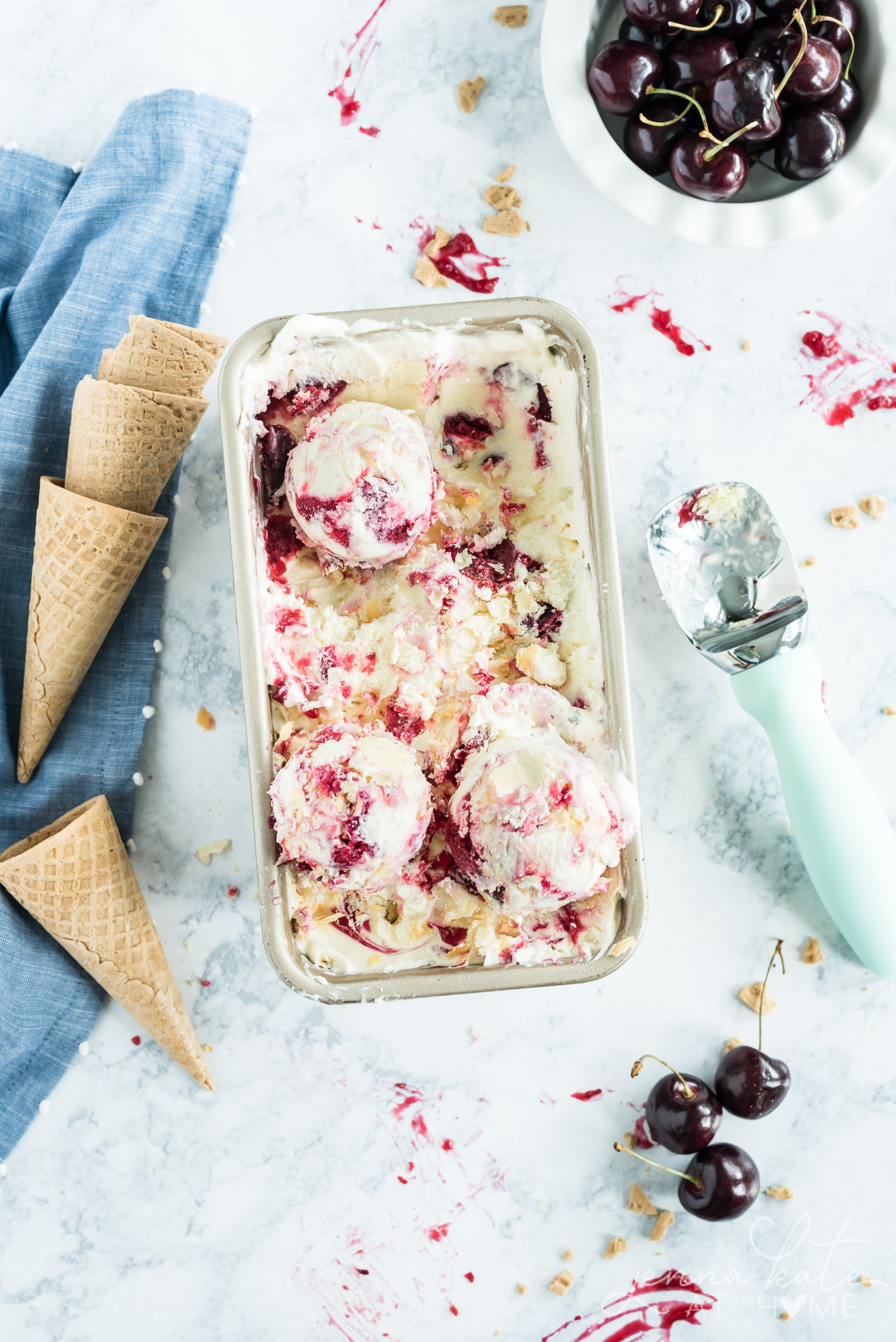 Overhead shot of cherry pie ice cream with scooped ice cream in the loaf pan full of ice cream