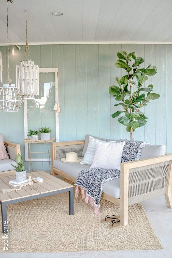 Coastal farmhouse style porch with neutral furniture and seafoam green walls