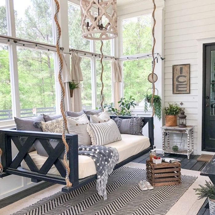 Daybed hanging from the ceiling of a  porch