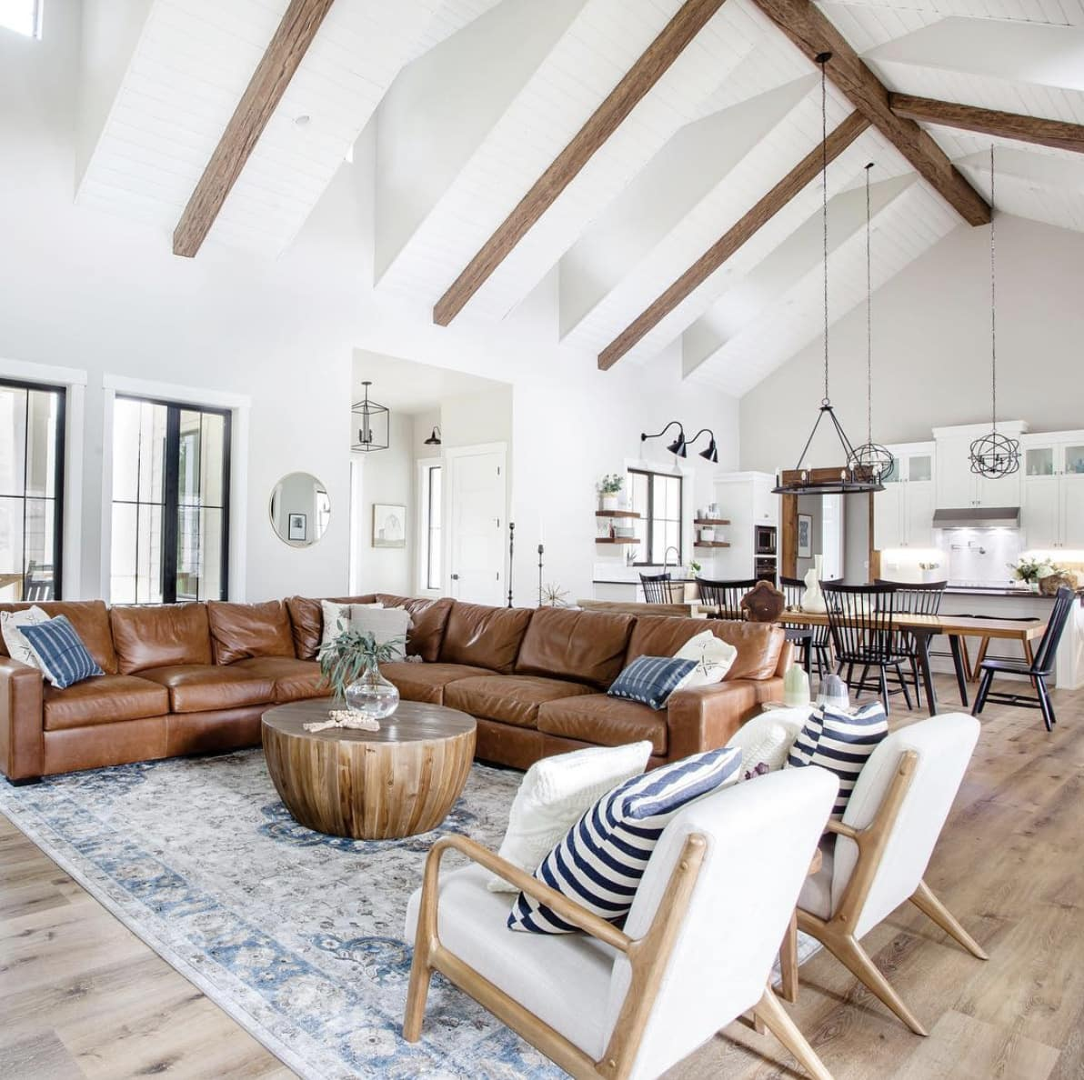 modern farmhouse-style great room with large living room rug placed under the sectional sofa and armchairs