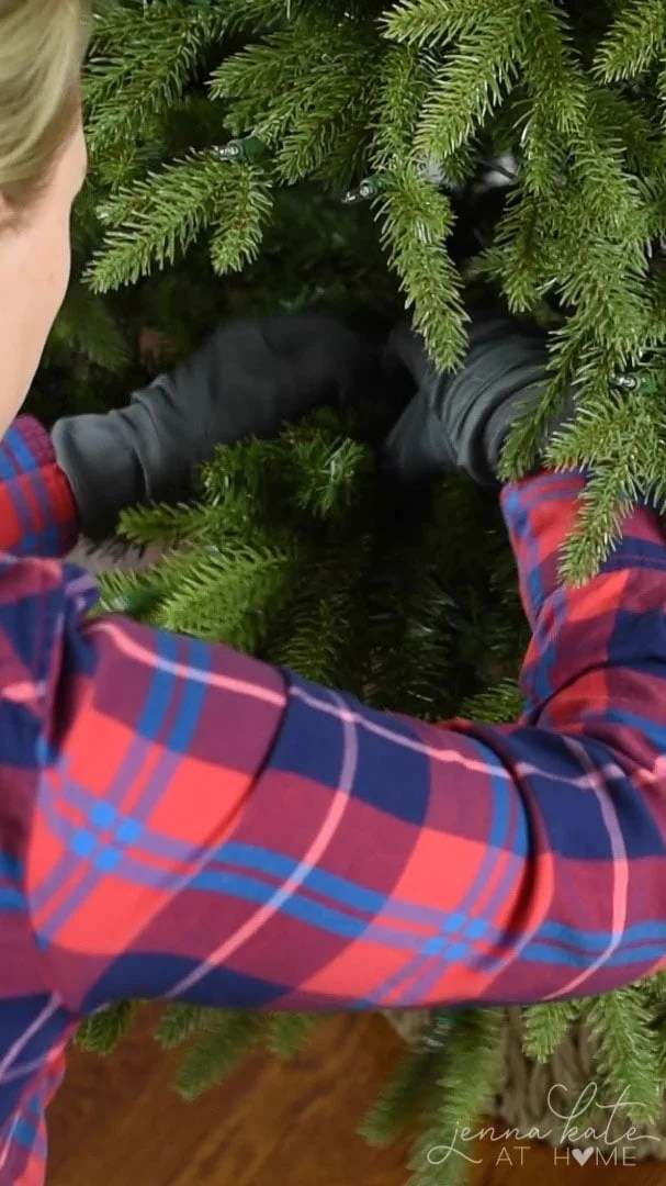 Fan out the branches on artificial Christmas tree