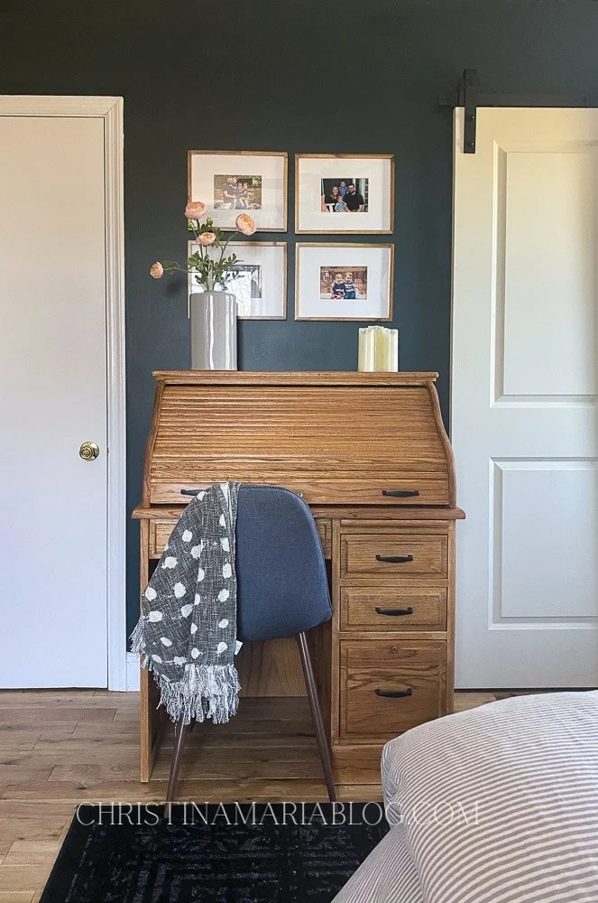 Dark green walls with oak desk in front of them