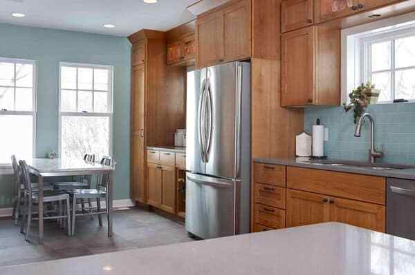 Honey oak kitchen cabinets with a soft blue green paint color on the walls
