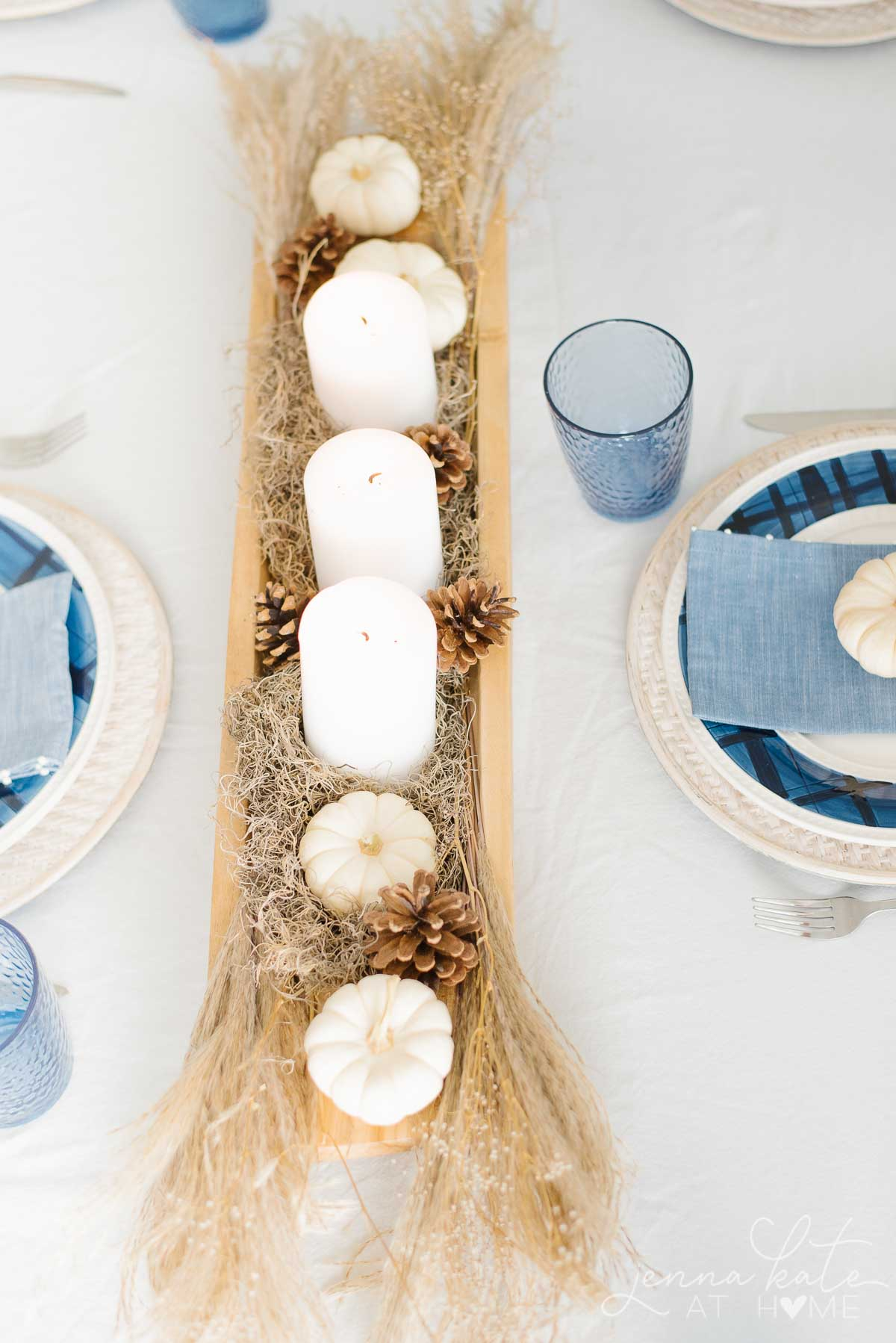 White candles and other neutral colored nature inspired objects in the centerpiece
