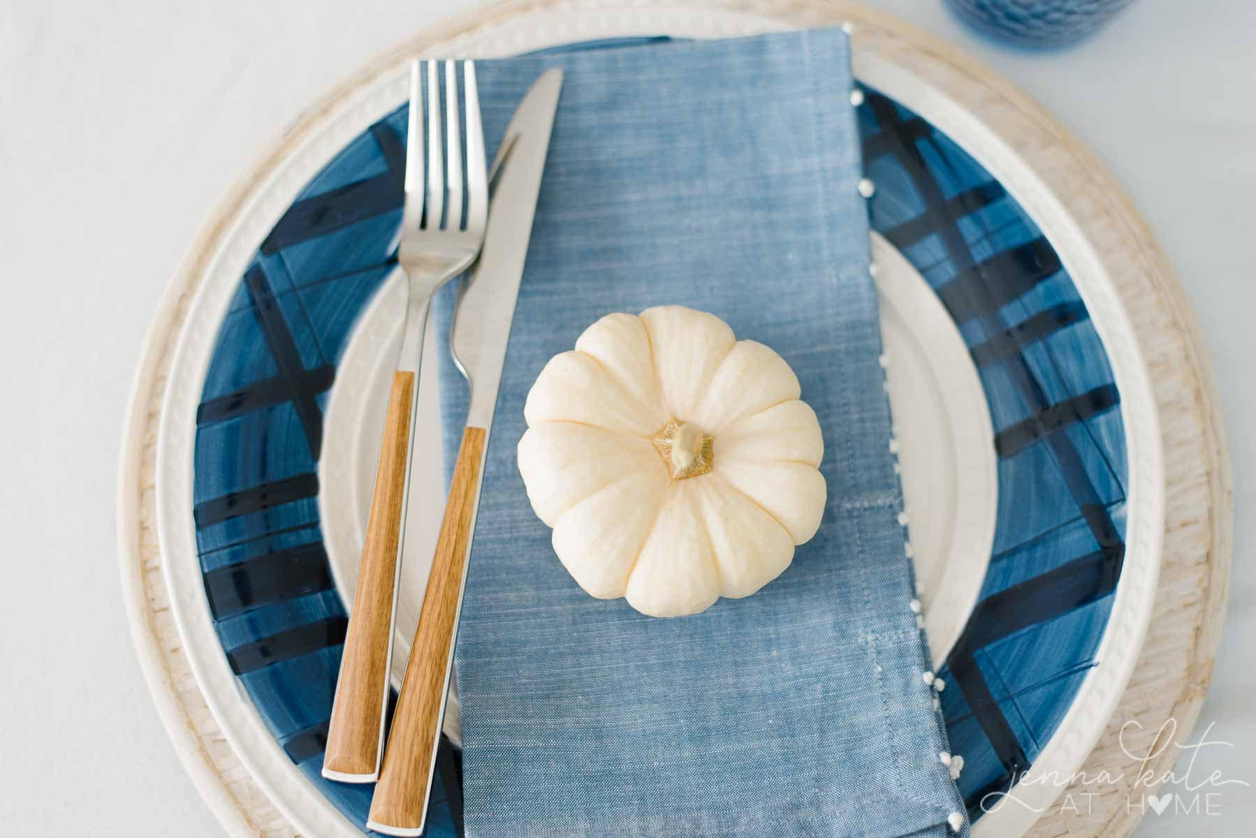 mini white pumpkin on a plate as part of a table setting inspired by nature