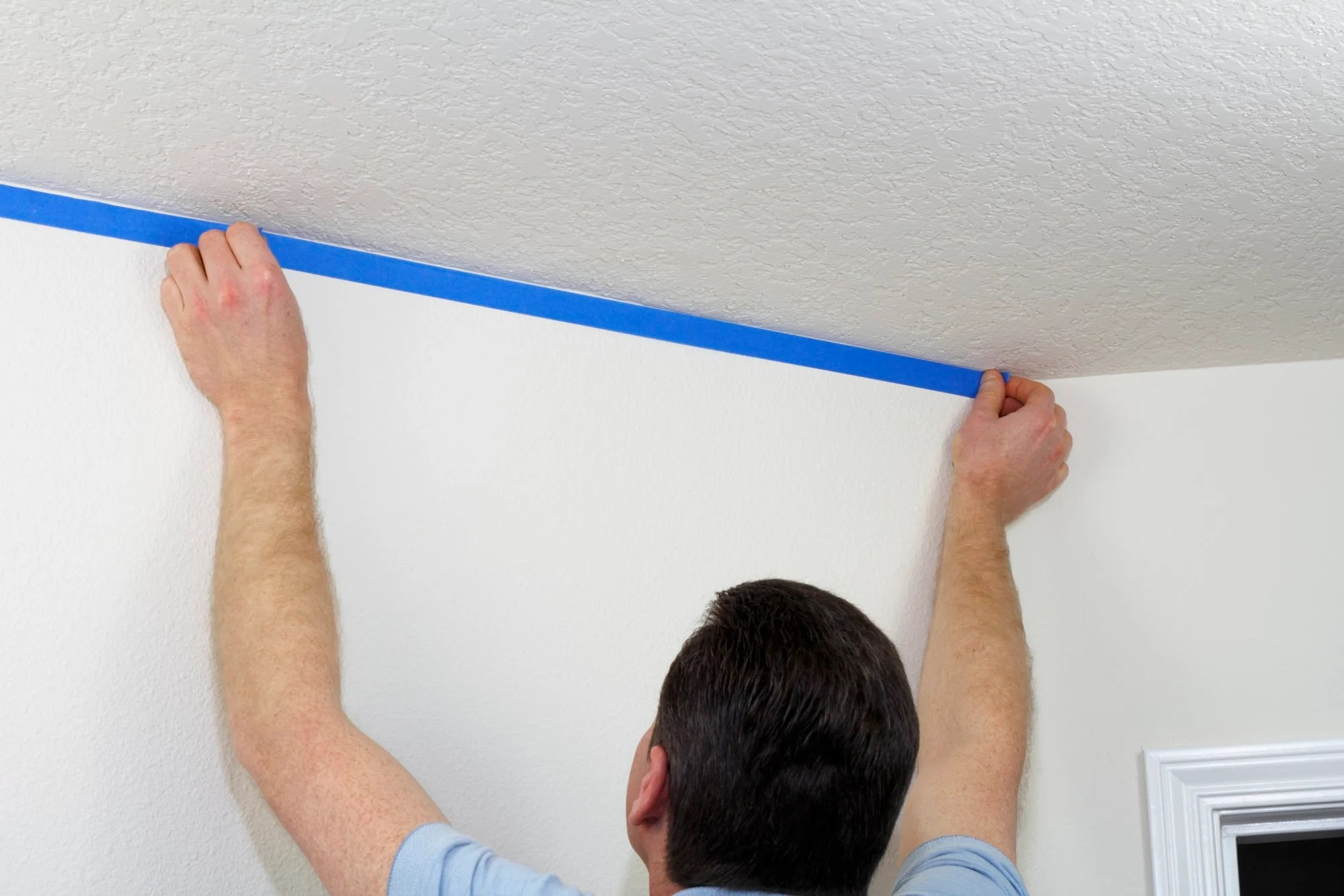 appy painter's tape to the ceiling and baseboards before painting