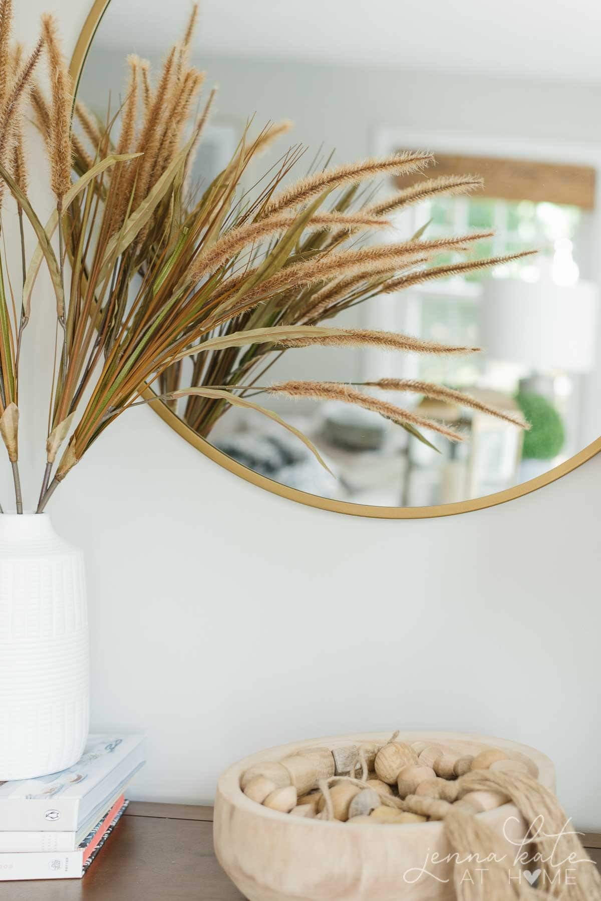 console table with mirror and dried grasses