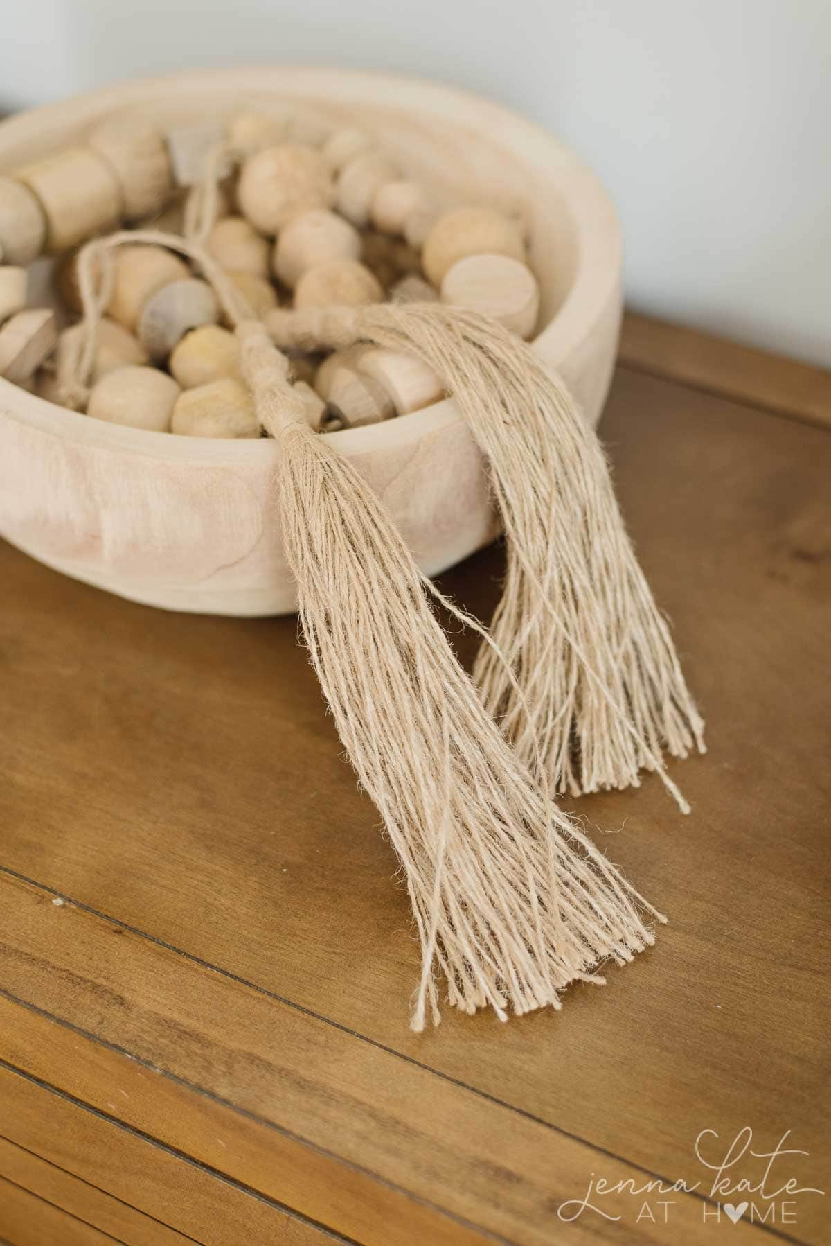 Wooden bowl with wood beads is uncluttered on a console table