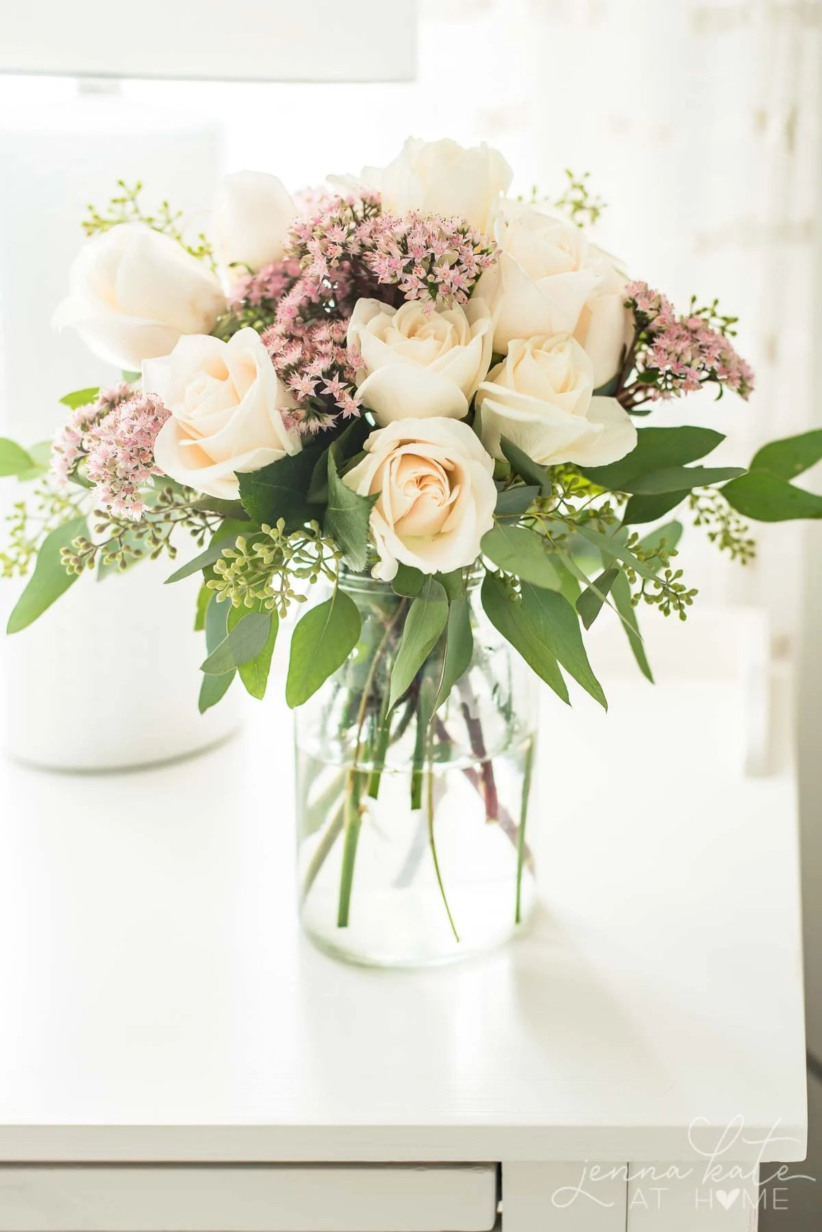 bouquet of roses, sedum and eucalyptus on bedroom nightstand