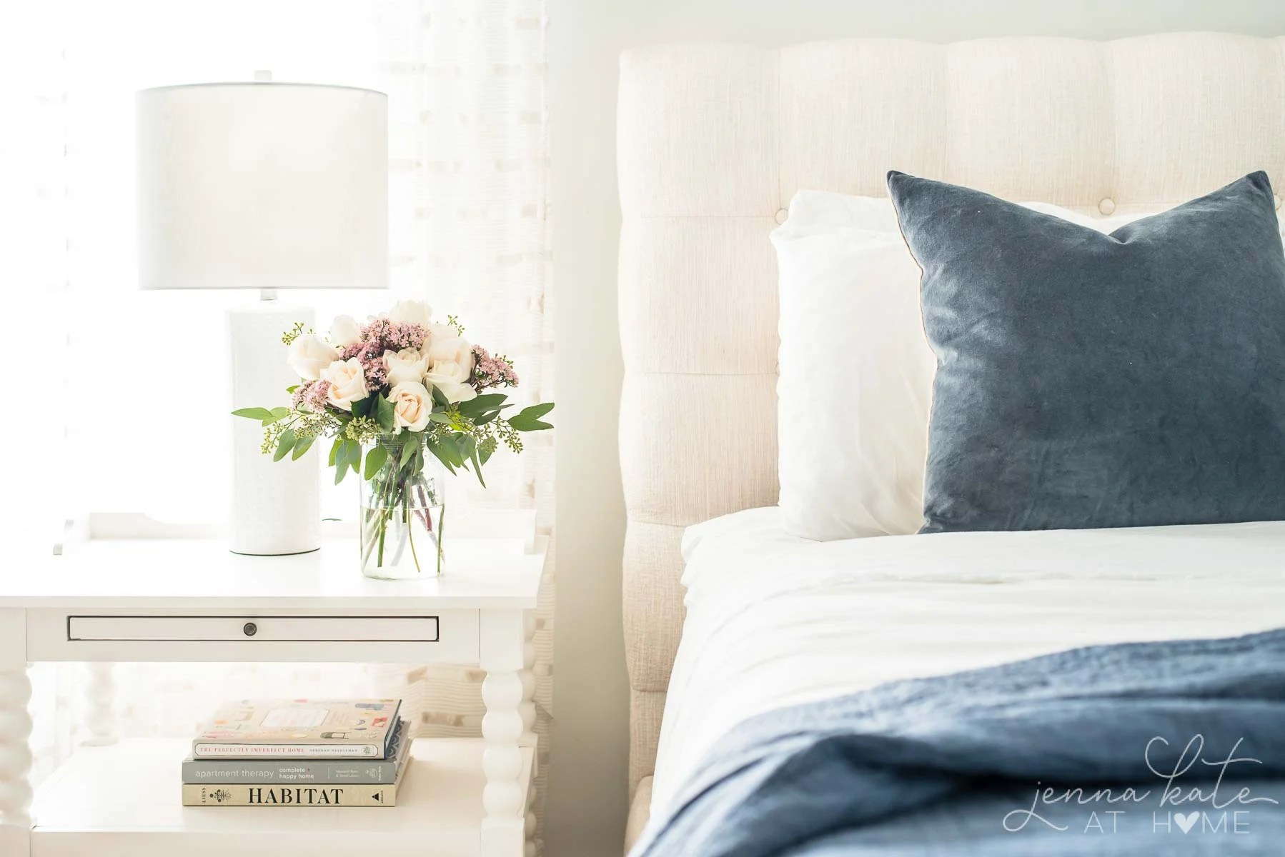 bed with fall flowers on the nightstand next to it
