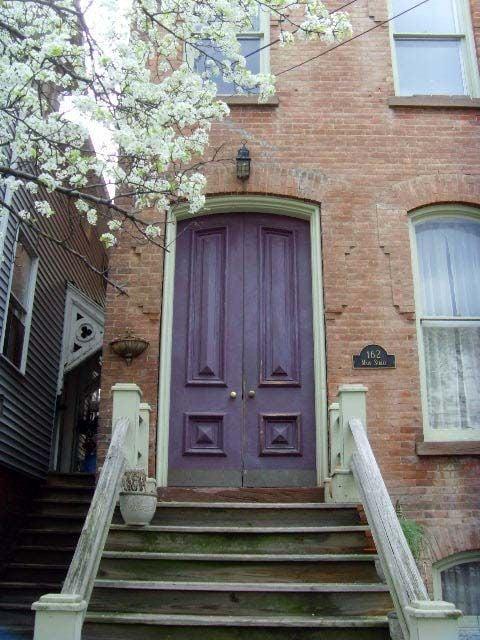 plum front door on red brick house