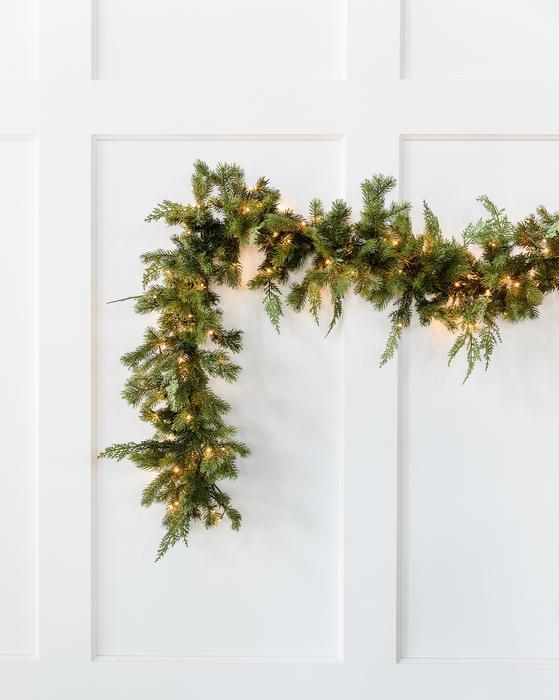 Pre-lit cedar garland against white wall