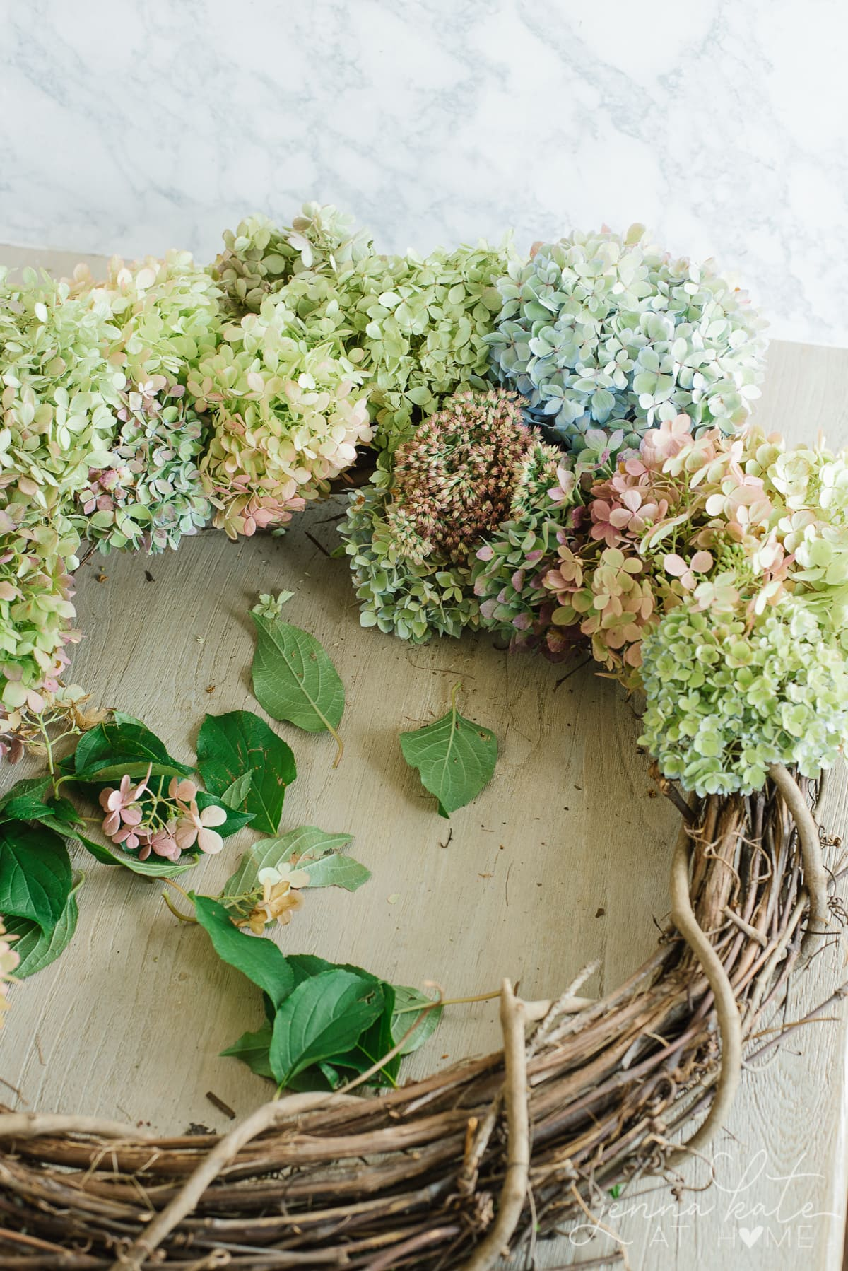A mixture of fresh and dried hydrangeas in different varieties and colors form the fall DIY wreath