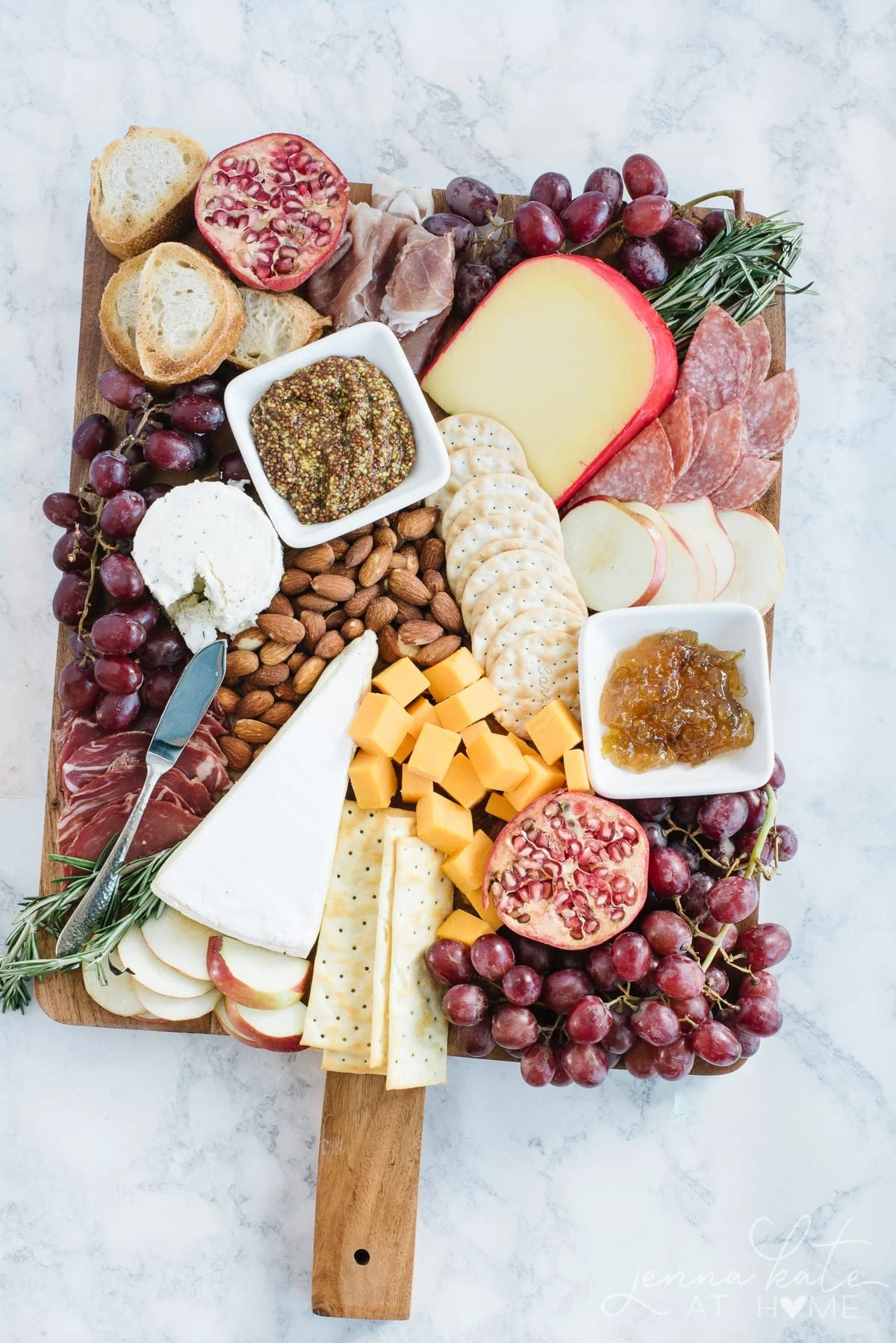 Charcuterie board for a wine tasting party filled with fruits, cheeses, meats and crackers