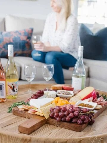 A woman sitting at a table with food and wine
